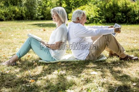 elderly couple sitting back to back