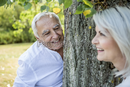 smiling elderly couple at a tree