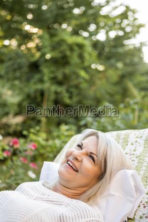 smiling mature woman relaxing in garden