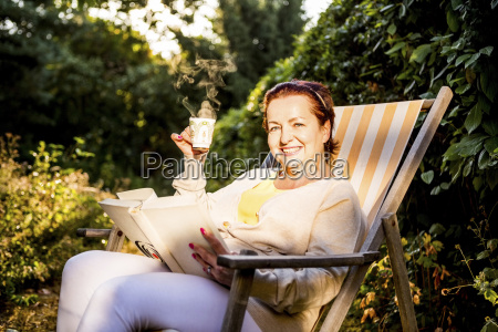 smiling mature woman reading book and