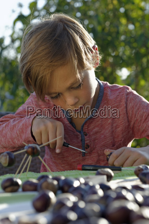 little boy tinkering chestnut figurines