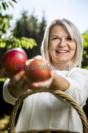 smiling mature woman holding apples outdoors