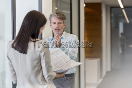 two business people discussing in corridor