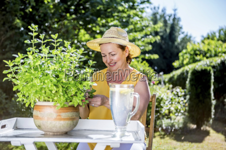 smiling mature woman caring for potted