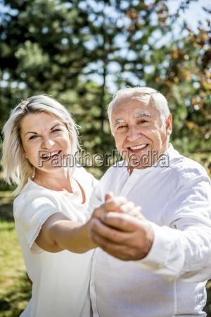 happy elderly couple dancing outdoors