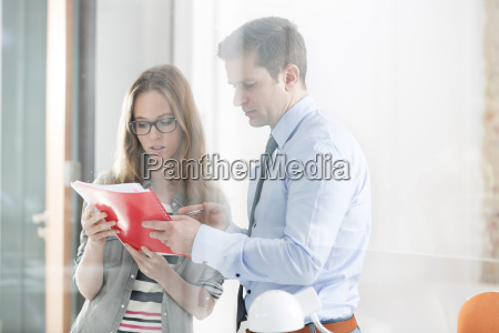 young woman and businessman discussing documents