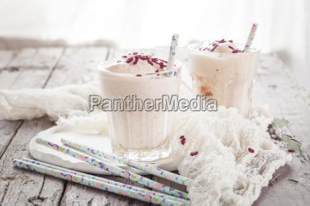 two glasses of vanilla milkshake with