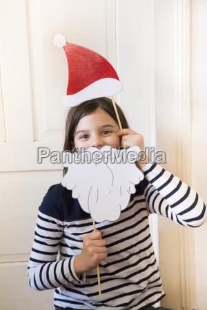portraet des maedchens mit weihnachtskappe und