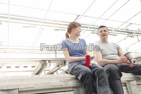 man and woman in greenhouse having