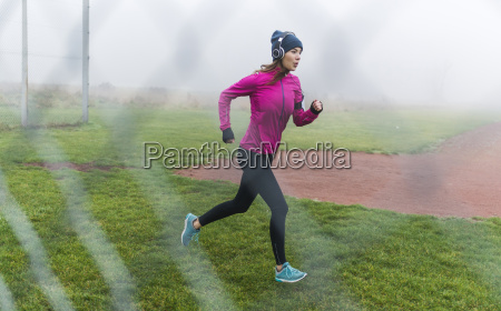 young woman with headphones jogging on
