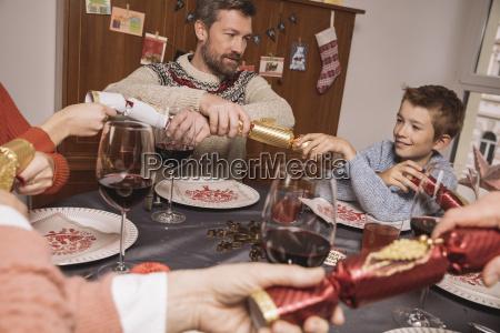 ziehen enden der weihnachtscracker am familientisch