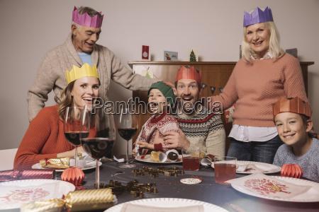 lustige drei generationen familienportraet mit papierkronen