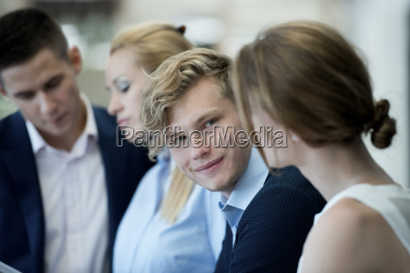 smiling businessman looking at female colleague