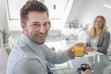 smiling man holding glass of orange