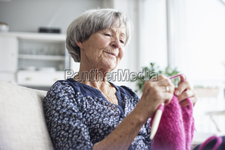 portraet stricken senior frau sitzt auf