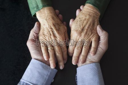 senior couple holding hands close up
