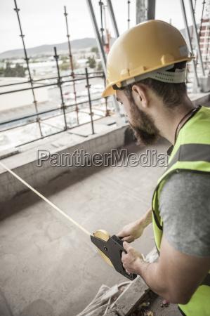 bauarbeiter mit massband in der baustelle