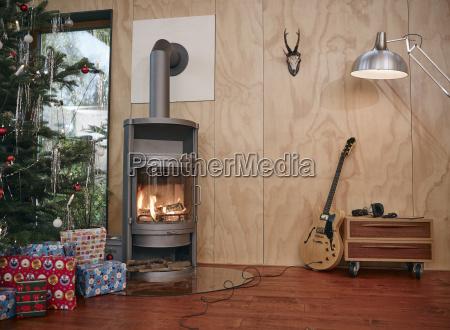 weihnachtsgeschenke unter weihnachtsbaum neben gemuetlichem kamin