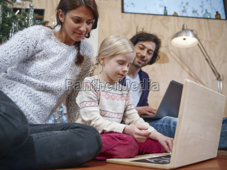 father using laptop mother playing with