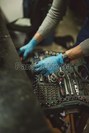 junge mechaniker aufnahme werkzeug aus dem