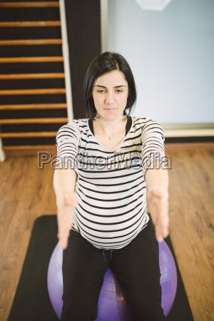 schwangere frau macht pilates UEbungen mit