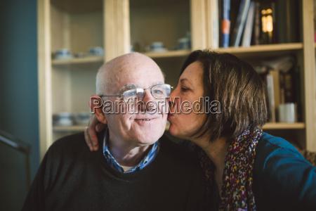 senior woman kissing her husband at