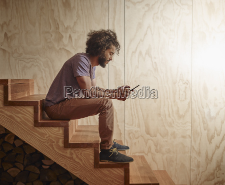 young man sitting on wooden stairs