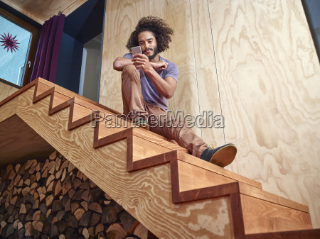 young man on wooden stairs looking