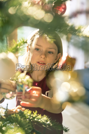 portrait of girl decorating christmas tree