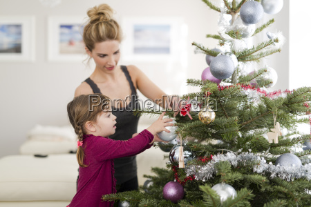 little girl decorating christmas tree with