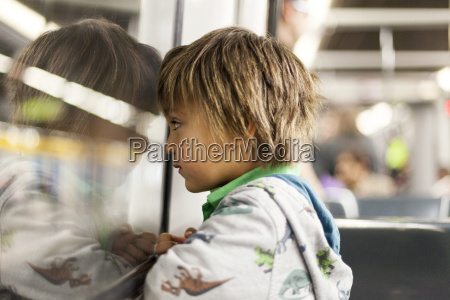 little boy looking through window of