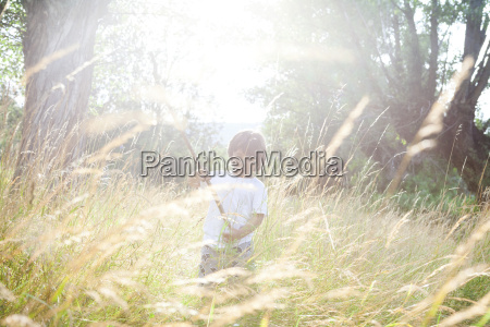 little boy with wood stick playing