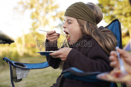 girl eating spaghetti on a camping
