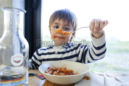 boy eating pasta with tomato sauce