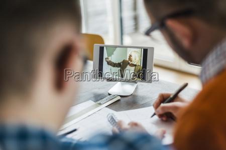 kollegen im buero beobachten videofilm auf