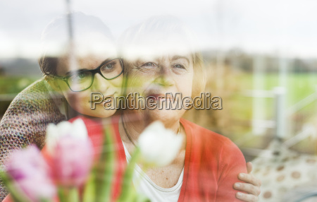 smiling young woman hugging senior woman