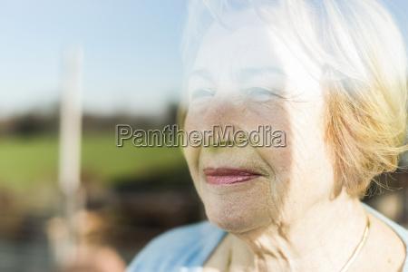 portrait of senior woman behind windowpane