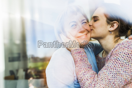 young woman kissing senior woman behind