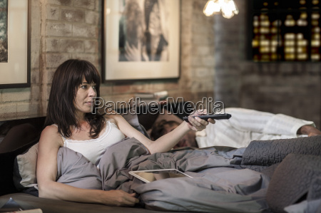 woman watching tv in bed with