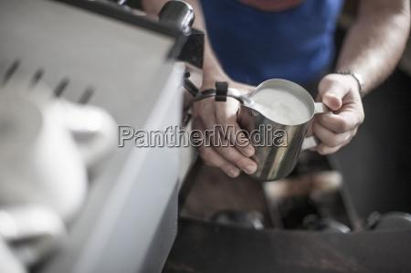 person die milchschaum fuer kaffee zubereitet