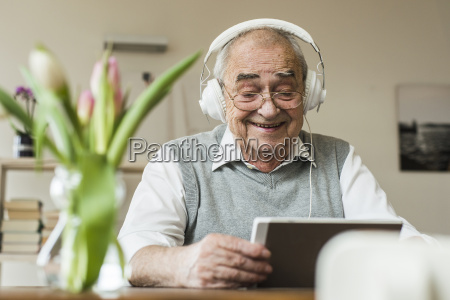 senior man using mini tablet and