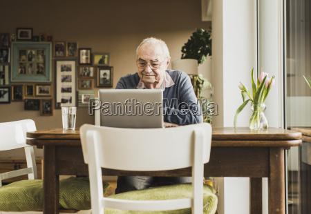 senior man sitting at table in