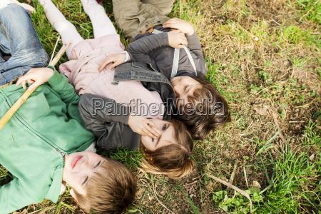 drei kinder liegen im gras