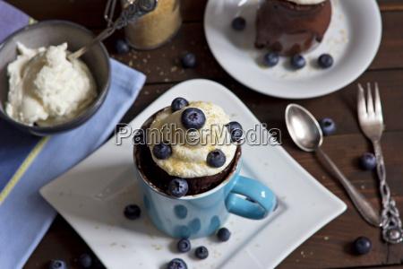 schokoladenkuchen mit schlagsahne rohrzucker und heidelbeeren