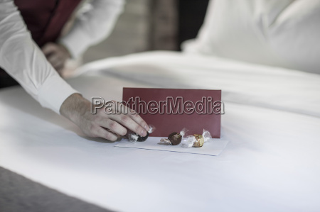 housekeeper putting chocolates on hotel bed