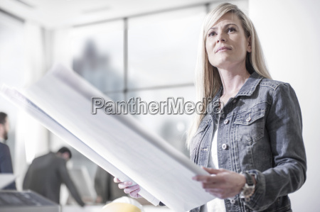 woman in office holding construction plan