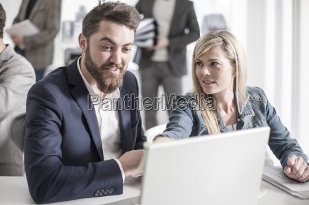 man and woman in office looking