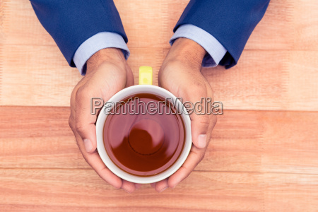 cropped hands of businessman holding coffee