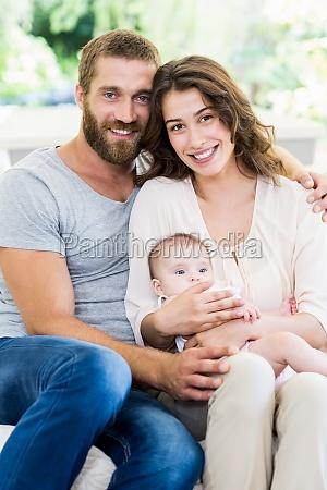 glueckliche eltern mit ihrem baby im