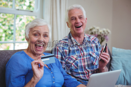cheerful senior couple with credit card